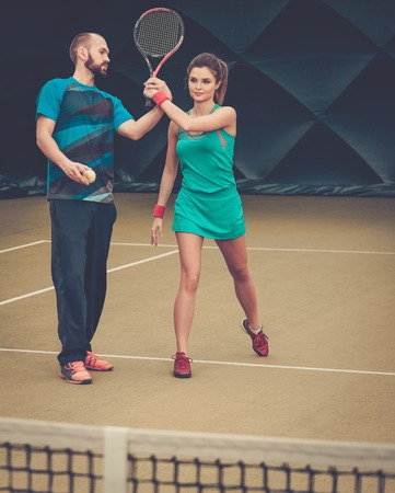 Woman player and her coach practicing on a tennis court photo