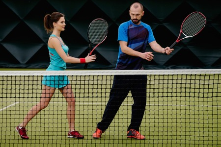 coach sport: Woman player and her coach practicing on a tennis court Stock Photo