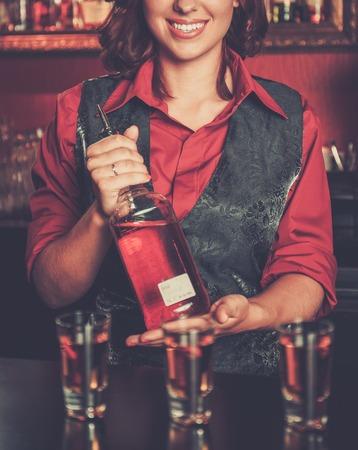 beautiful redhead: Beautiful redhead barmaid making shots