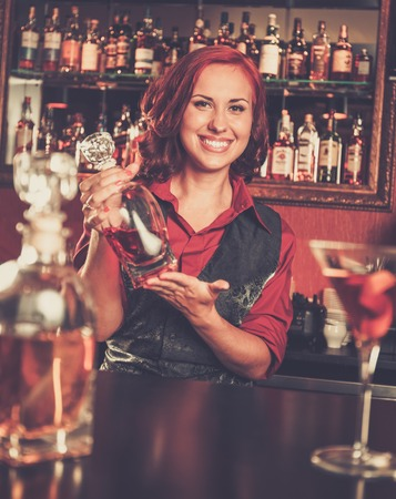 barmen: Beautiful redhead barmaid with bottle behind bar counter