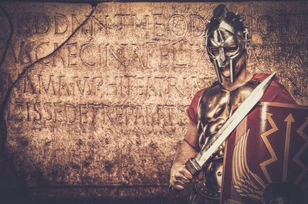 the romans: Roman legionary soldier in front of  wall with ancient writing