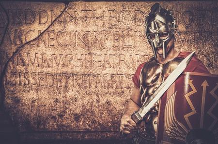 Soldato legionario romano di fronte al muro con l'antica scrittura