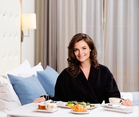 breakfast room: Beautiful woman having breakfast in a hotel room