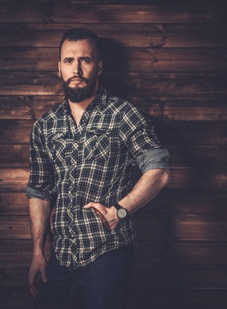 trimmed: Handsome man wearing checkered  shirt in wooden rural house interior
