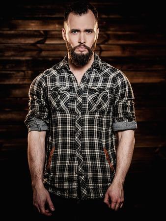 flannel: Handsome man wearing checkered  shirt in wooden rural house interior