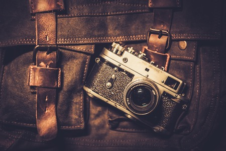 Vintage camera and handbag on wooden background