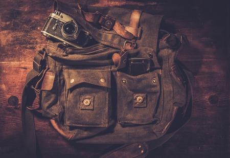Vintage camera and handbag on wooden background photo