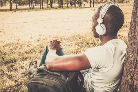 personas escuchando: Sonriente joven afroamericano escucha la m�sica en un parque