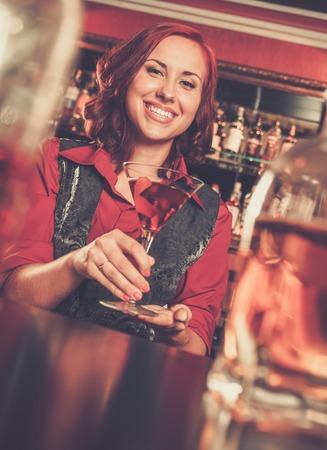 beautiful redhead: Beautiful redhead barmaid with cocktail behind bar counter Stock Photo