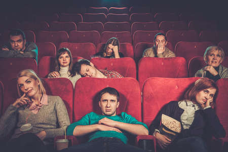 theater audience: Group of people watching boring movie in cinema