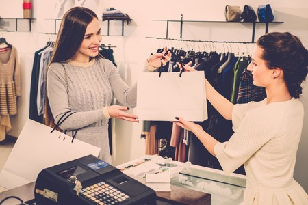 customer assistant: Happy customer with shopping bag in fashion showroom Stock Photo