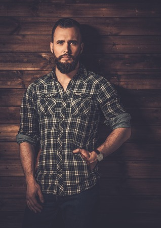 rugged: Handsome man wearing checkered  shirt in wooden rural house interior