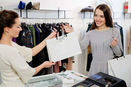 retail occupation: Happy customer with shopping bag in fashion showroom Stock Photo