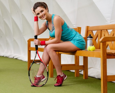 Young woman resting on a bench after tennis workout photo