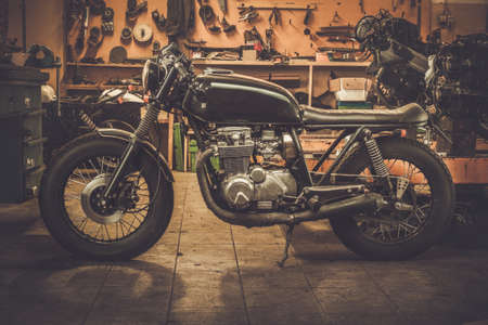 Vintage style cafe-racer motorcycle in customs garage Imagens
