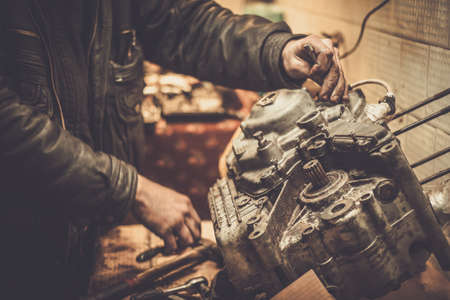 dirty old man: Mechanic working with with motorcycle engine in a workshop Stock Photo