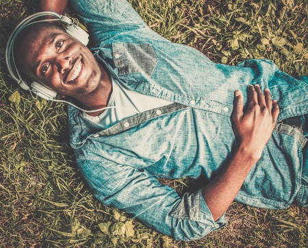 american music: Smiling young african american listens music in a park Stock Photo