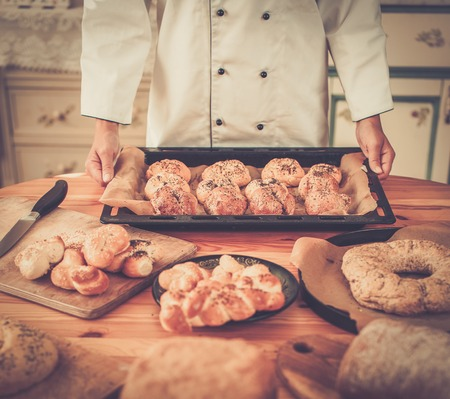 white goods: Cook hands holding baking tray with homemade baked goods
