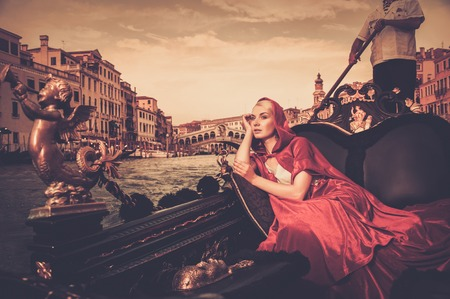 Beautiful woman in red cloak riding on gondola photo