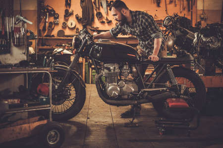 garage: Mechanic building vintage style cafe-racer motorcycle  in custom garage Stock Photo