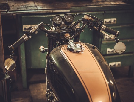 custom built: Vintage style cafe-racer motorcycle in customs garage Stock Photo