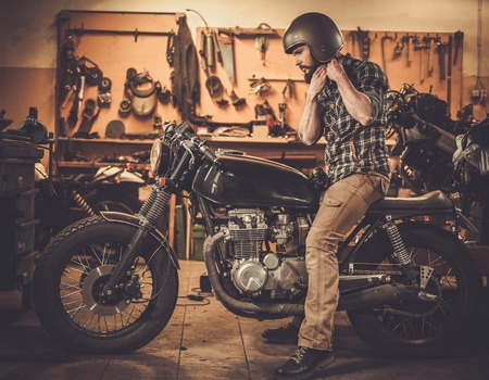 motorcycles: Rider and his vintage style cafe-racer motorcycle in customs garage