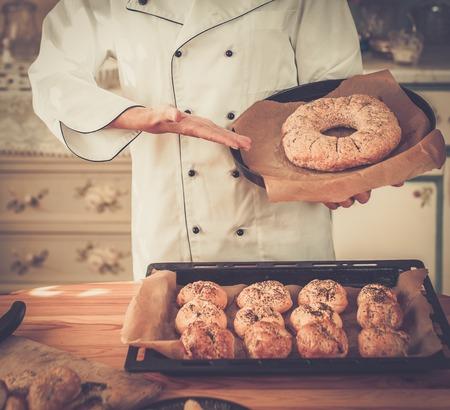 haciendo pan: Manos cocine la celebración de productos horneados caseros Foto de archivo