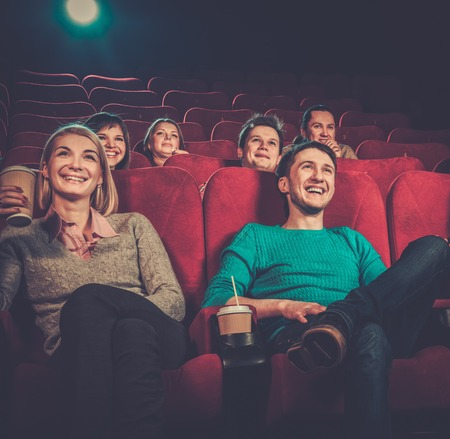 funny movies: Group of smiling people watching movie in cinema