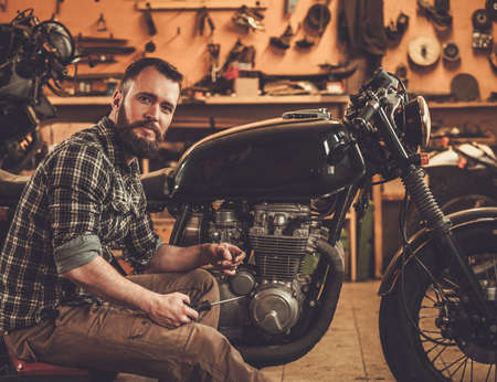carb: Mechanic building vintage style cafe-racer motorcycle  in custom garage Stock Photo