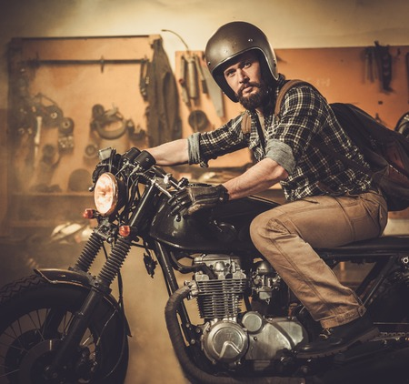 handlebars: Rider and his vintage style cafe-racer motorcycle in customs garage