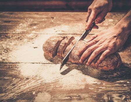 haciendo pan: Cortar el pan hecho en casa sobre una mesa Hombre Foto de archivo