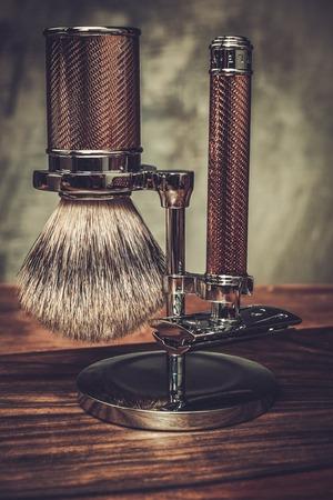peluquero: Maquinilla de afeitar y brocha de afeitar en un soporte