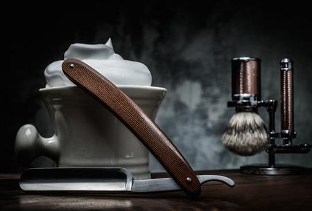 barbero: Las maquinillas de afeitar y plato con espuma en el fondo de madera