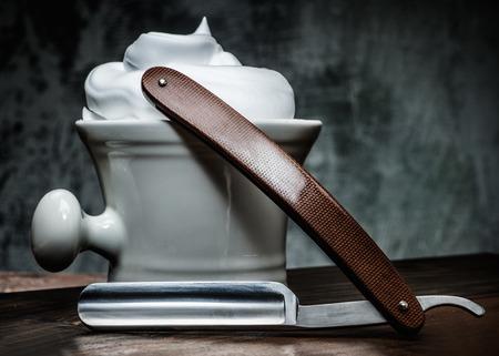 Shaving bowl and straight razor on wooden background photo