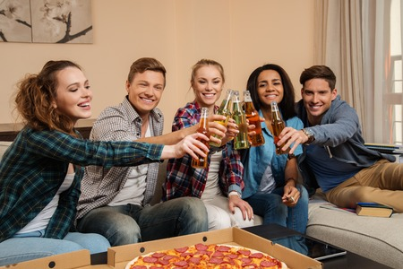 chat group: Group of young multi-ethnic friends with pizza and bottles of drink celebrating in home interior