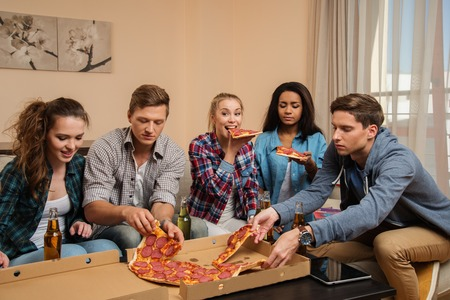 students fun: Group of young multi-ethnic friends with pizza and bottles of drink celebrating in home interior