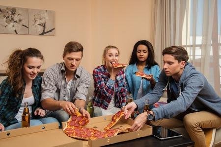 Gruppe der jungen multiethnischen Freunde mit Pizza und Getränkeflaschen feiert in home interior Standard-Bild