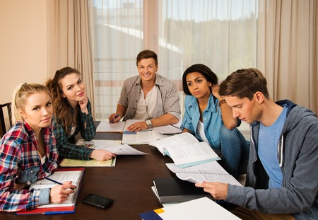 final examination: Multi ethnic group of students preparing for exams in home interior behind table Stock Photo