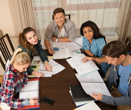 Multi ethnic group of students preparing for exams in home interior behind table Stock Photo