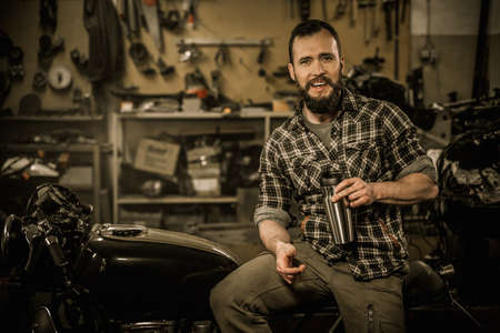 helmet seat: Rider and his vintage style cafe-racer motorcycle in customs garage