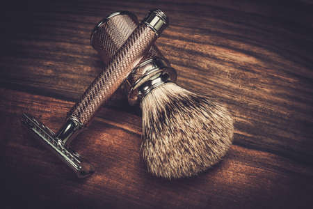 barbers: Safety razor and shaving brush on a wooden background