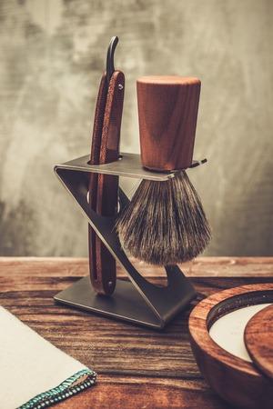 barbero: Maquinilla de afeitar y brocha de afeitar en un soporte