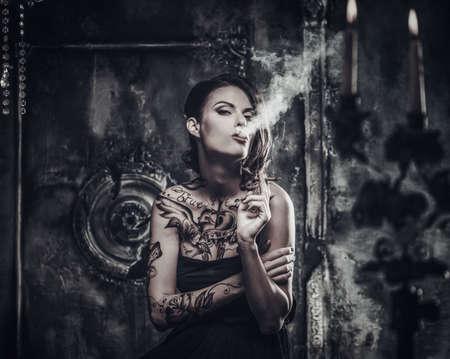 donna sexy: Fumare tatuato bella donna in interni vecchi spettrale