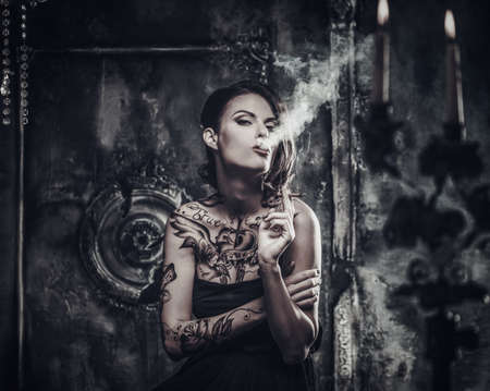 scary girl: Smoking tattooed beautiful woman  in old spooky interior