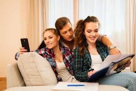 Three young students preparing for exams in apartment interior photo