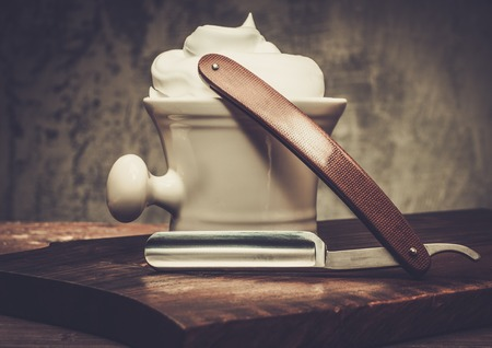 straight razor: Shaving bowl and straight razor on wooden background