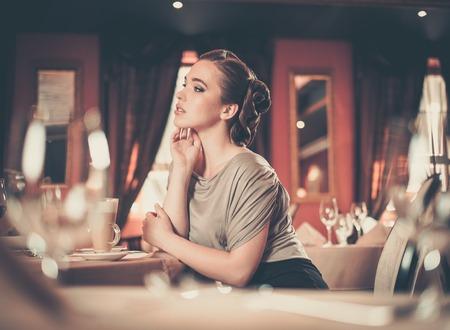 Beautiful young girl in luxury restaurant interior photo