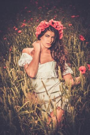 chaplet: Brunette girl wearing white summer dress and flower chaplet in poppy filed