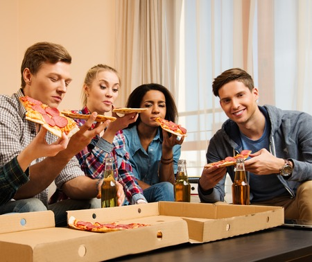 Group of multi-ethnic friends with pizza and bottles of drinks having party photo