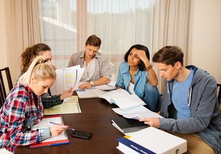 Multi ethnic group of students preparing for exams in home interior behind table photo